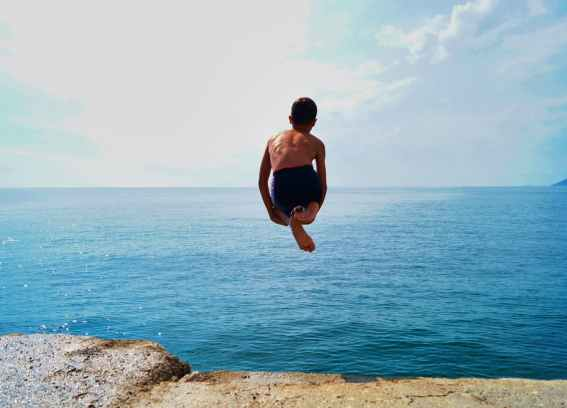 taking the leap : boy over ocean